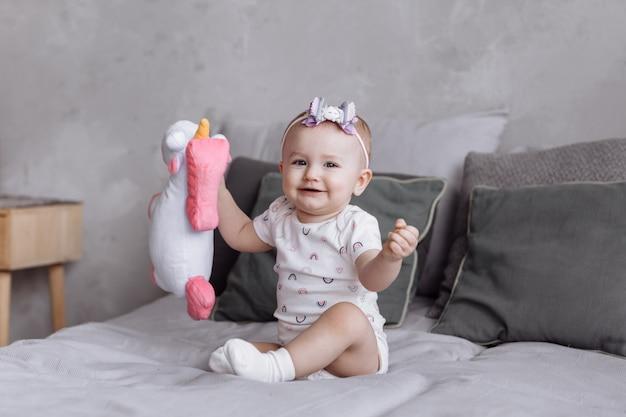 Entzückendes kleines mädchen spielt mit spielzeug-einhorn auf dem bett zu hause. konzept des kindheitstages. glückliches baby, familientag
