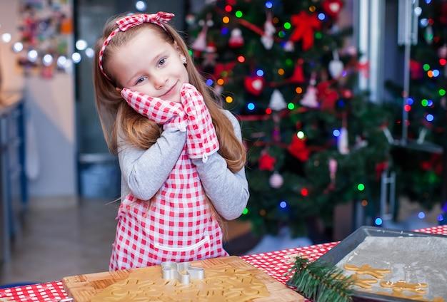 Entzückendes kleines mädchen trug herein die handschuhe, die weihnachtslebkuchenplätzchen backen