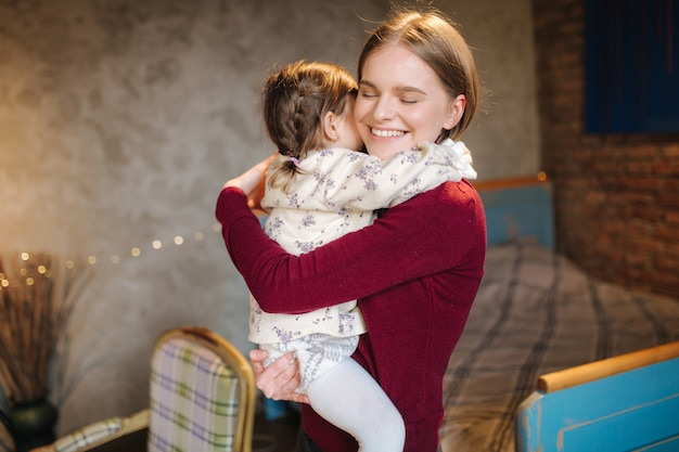 Entzückendes kleines mädchen umarmen ihr schönes und junges patinporträt der glücklichen frau umarmen sie
