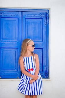 Entzückendes kleines mädchen vor blauer tür draußen am typischen griechischen traditionellen dorf auf mykonos in griechenland