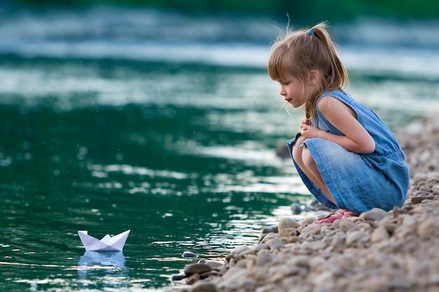 Entzückendes kleines nettes blondes mädchen im blauen kleid auf den riverbankkieseln, die mit weißbuchorigamiboot auf blauem funkelndem bokeh wasserhintergrund spielen. träume und fantasien des glücklichen kindheitskonzeptes.