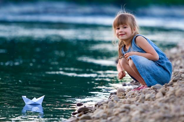 Entzückendes kleines süßes blondes mädchen im blauen kleid auf flussuferkieselsteinen, die mit origami-boot des weißen papiers auf blau funkelndem bokeh-wasser spielen. träume und fantasien eines glücklichen kindheitskonzepts.
