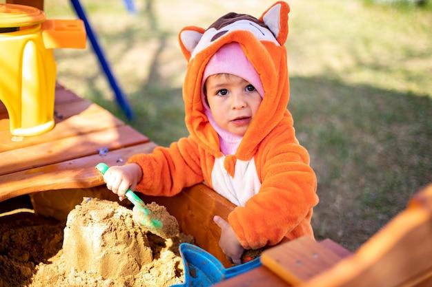 Entzückendes kleinkind, das im sandkasten spielt, süßes kind im fuchspyjama spielt im sandporträt von a