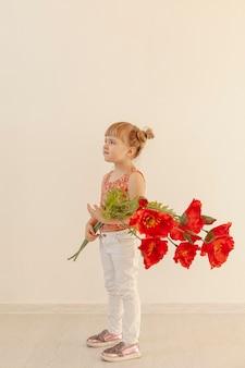 Entzückendes kleinkind, das mit blume aufwirft