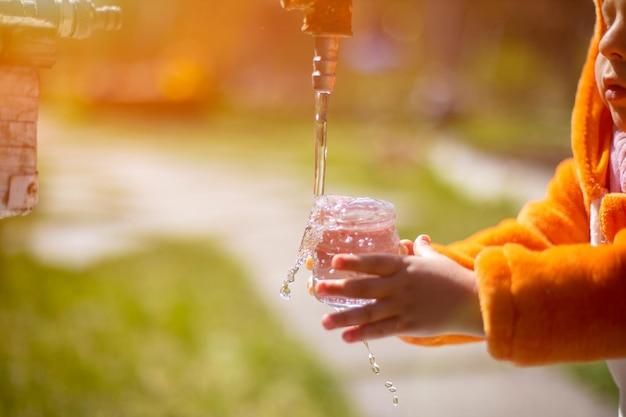 Entzückendes kleinkind spielt mit wasser und wasserhahn in der sonne