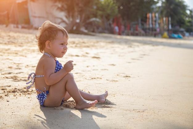 Entzückendes kleinkindmädchen, das am sandstrand der tropischen insel spielt. sommerferien
