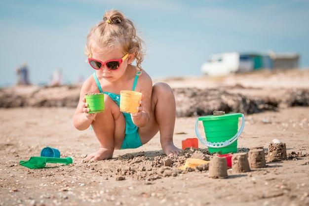 Entzückendes kleinkindmädchen, das auf weißem sandstrand spielt