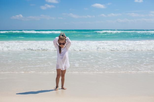 Entzückendes kleinkindmädchen im weißen kleid gehend am exotischen strand
