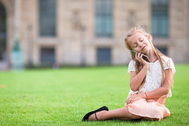 Entzückendes kleinkindmädchen mit telefon in paris während der sommerferien