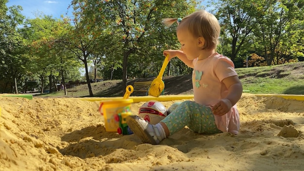 Entzückendes kleinkindmädchen spielt im sandkasten mit spielzeugsommerzeit in 4k