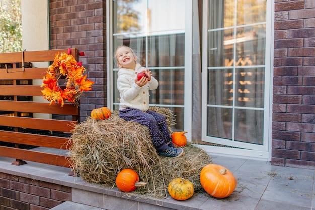 Entzückendes lachendes kaukasisches babykleinkind in der weißen strickjacke, die auf dem heuschober mit kürbisen am portal sitzt und mit apfel spielt.