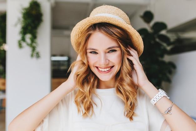 Entzückendes lachendes mädchen, das silbernes armband und weiße armbanduhr trägt, die aufwirft