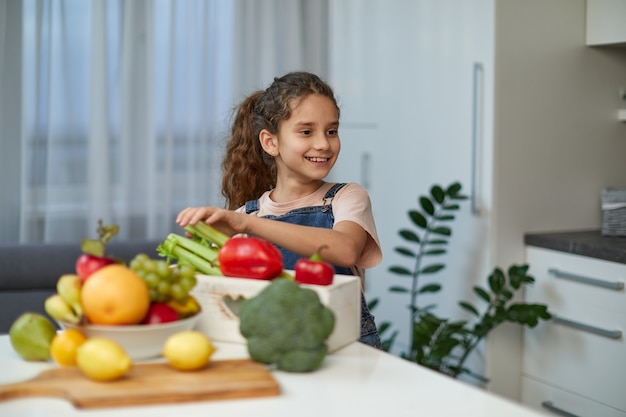 Entzückendes lachendes und lockiges kleines mädchen sitzt am tisch in der küche, in der nähe von gemüse.
