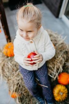 Entzückendes lächelndes kaukasisches babykleinkind in der weißen strickjacke, die auf dem heuschober mit kürbisen am portal sitzt und mit apfel spielt.