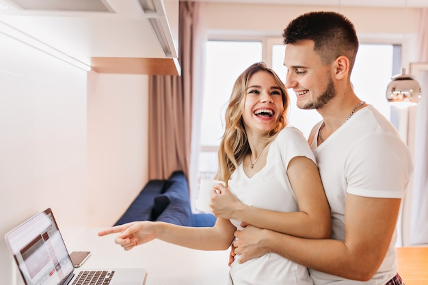 Entzückendes lächelndes mädchen, das finger auf laptop-bildschirm zeigt. innenaufnahme des lachenden paares, das lustiges video sieht.