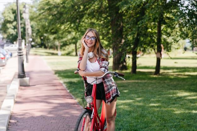 Entzückendes lächelndes mädchen, das im park mit fahrrad aufwirft. foto im freien der entspannten dame, die auf natur aufwirft.