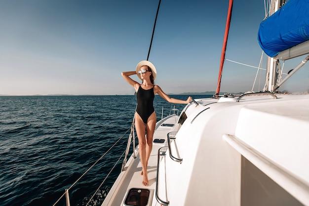 Entzückendes langbeiniges junges model, das einen schwarzen engen bikini-body, eine sonnenbrille und einen panamahut trägt und auf ihrer schlaffen weißen yacht posiert