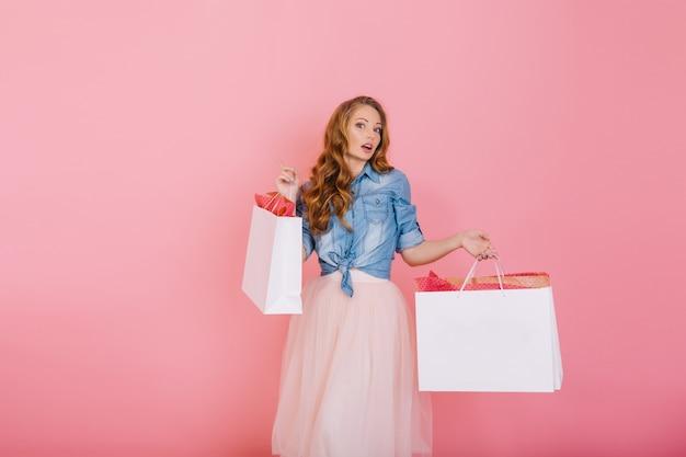 Entzückendes langhaariges stilvolles mädchen im trendigen rock, der papiertüten von der boutique mit überraschtem gesichtsausdruck hält. porträt der gelockten jungen frau, die nach dem einkaufen lokalisiert auf rosa hintergrund aufwirft