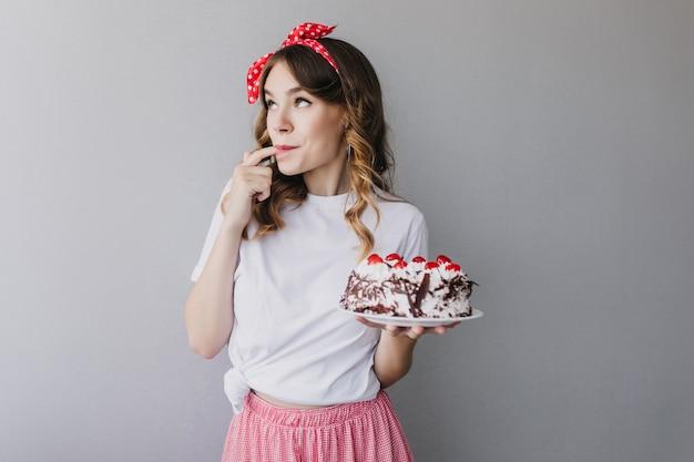 Entzückendes lockiges mädchen, das erdbeerkuchen schmeckt. innenaufnahme des romantischen weiblichen modells mit rotem band im haar, das leckeren kuchen hält.
