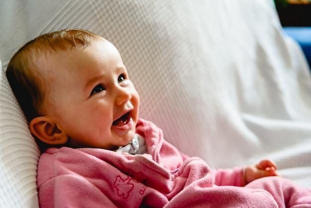 Entzückendes lustiges baby, das mit rosa pyjamas lächelt.