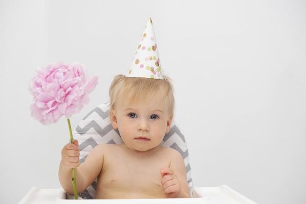 Entzückendes lustiges kaukasisches blondes baby, das am hochstuhl sitzt und geburtstagshut trägt, der rosa pionblume auf hellgrauem hintergrund hält. idee der partei für kind, grußkarte. kleinkind, das feiertag feiert.