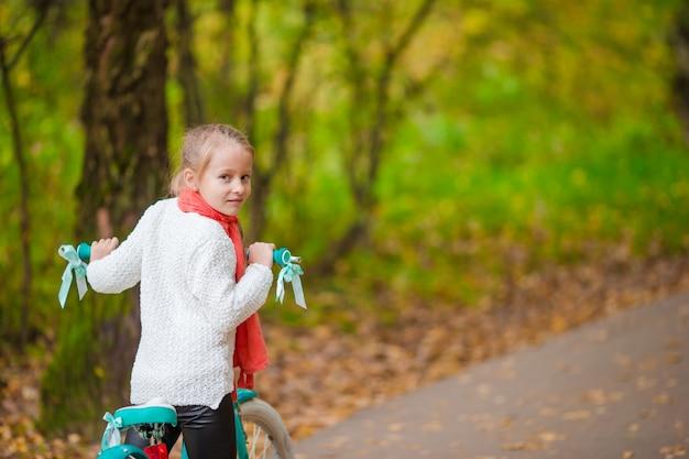 Entzückendes mädchen, das draußen ein fahrrad am schönen herbsttag reitet
