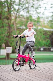 Entzückendes mädchen, das draußen ein fahrrad am schönen sommertag reitet