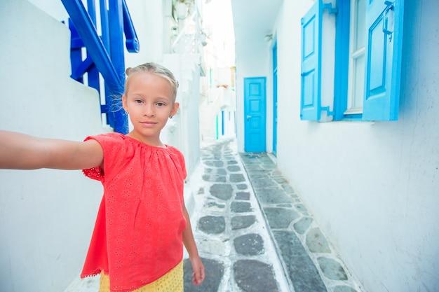 Entzückendes mädchen, das draußen selbstporträt im griechischen dorf nimmt