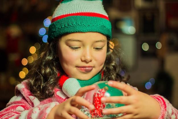 Entzückendes mädchen, das ihre weihnachtsglaskugel hält und betrachtet