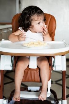 Entzückendes mädchen, das im kinderstuhl und -essen sitzt