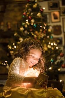 Entzückendes mädchen, das lächelt und ihr weihnachtsgeschenk betrachtet
