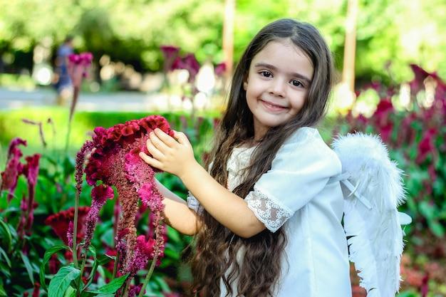 Entzückendes mädchen, das nach dem taufritual amaranthblume im garten mit leuchtenden farben berührt