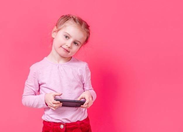 Entzückendes mädchen, das smartphone über rosa hintergrund verwendet