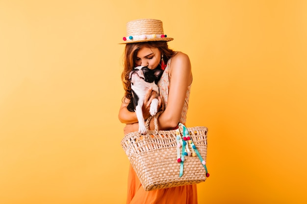 Entzückendes mädchen im strohsommerhut, das ihren hund küsst. stilvolle ingwerfrau, die mit welpen auf gelb aufwirft.