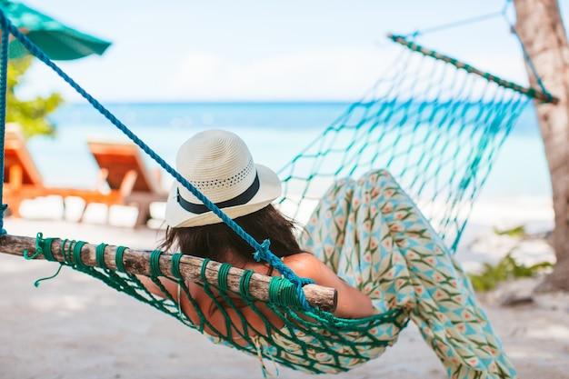 Entzückendes mädchen im tropischen urlaub, der in der hängematte entspannt