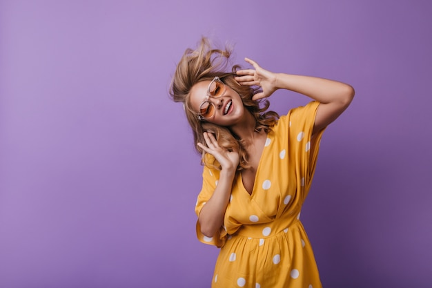 Entzückendes mädchen in der orange kleidung, die tanzt, während musik hört. blonde frau genießt lieblingslied.