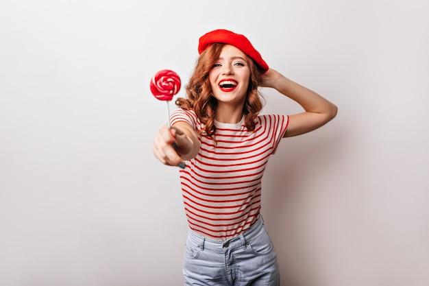 Entzückendes mädchen in der roten baskenmütze, die süßigkeiten isst. erstaunliche französische dame mit ingwerhaar, das mit lutscher aufwirft.