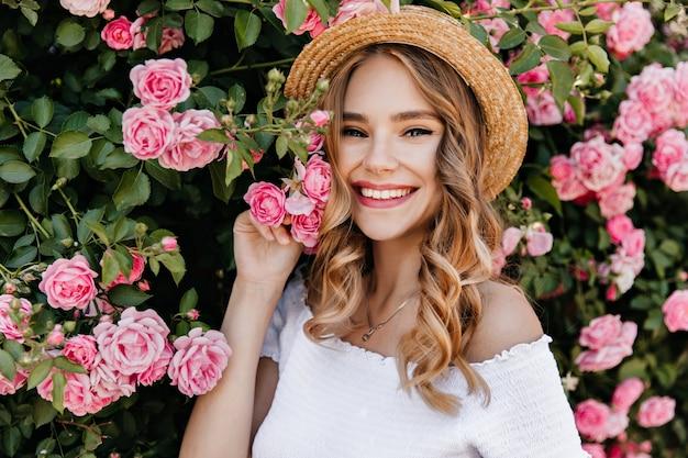 Entzückendes mädchen mit dem lockigen blonden haar, das im garten aufwirft. porträt der kaukasischen frohen frau, die rosa blume hält.