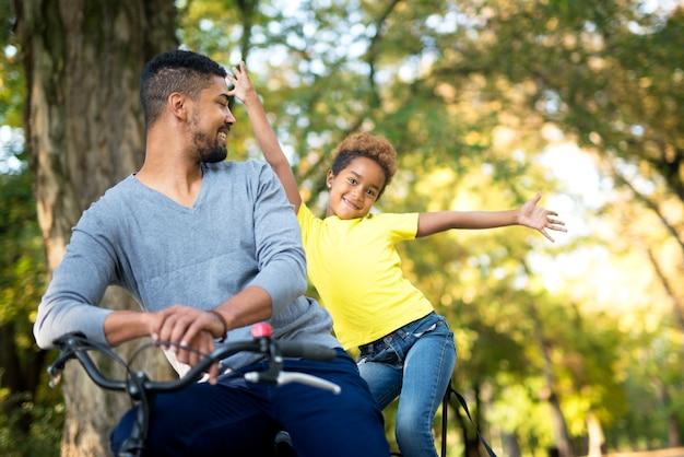 Entzückendes mädchen mit erhobenen armen und vater auf einem fahrrad, das im park genießt