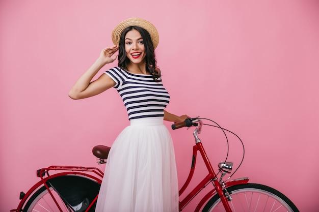 Entzückendes mädchen mit gewelltem haar, das nahe rotem fahrrad steht. innenfoto der angenehmen schlanken frau im hut, der positive gefühle ausdrückt.