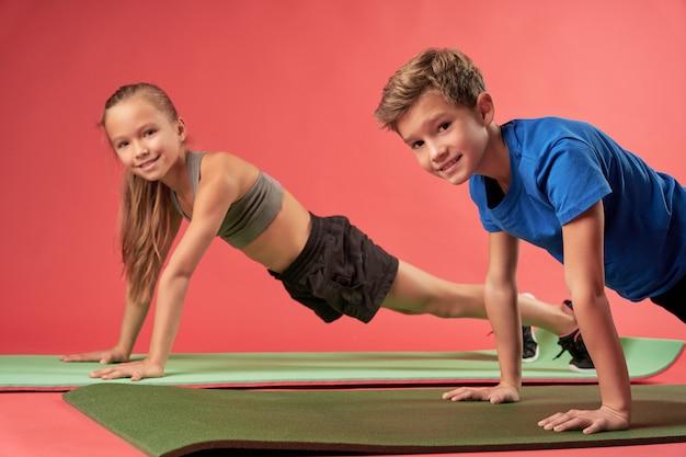 Entzückendes mädchen und junge in sportkleidung, die eine liegestützposition halten und lächeln, während sie kraftübungen auf yogamatten machen