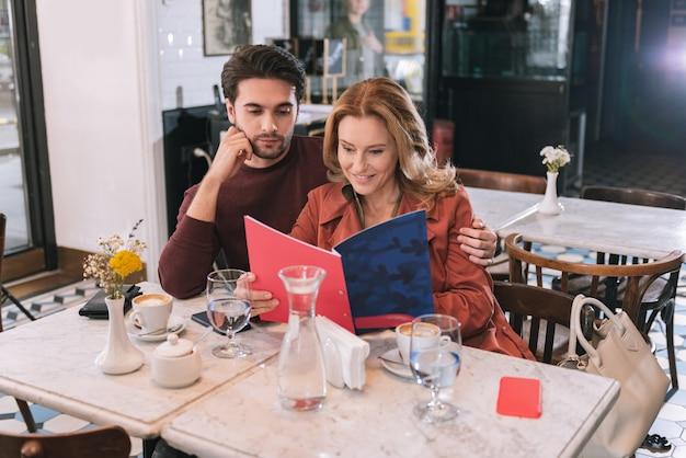 Entzückendes nettes paar, das menü liest und am tisch sitzt