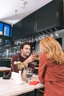 Entzückendes nettes paar, das wein trinkt und sich unterhält