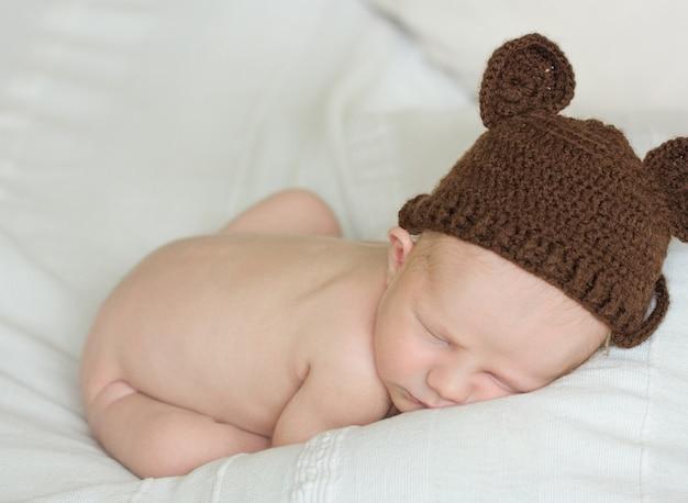 Entzückendes neugeborenes baby, das im gemütlichen raum schläft. nettes glückliches säuglingsbabyporträt mit schläfrigem gesicht im bett. weichzeichner an den babyaugen. neugeborene kinderbetreuung und wiegenlied