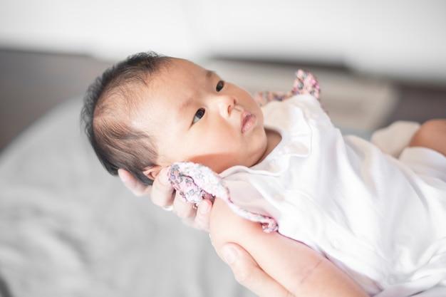 Entzückendes neugeborenes baby, das in den mutterarmen stillsteht.