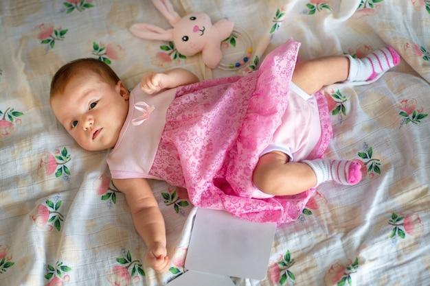 Entzückendes neugeborenes baby im rosa kleid