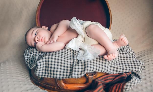 Entzückendes neugeborenes, das über einer karierten decke auf einem vintage-reisekoffer liegt lying