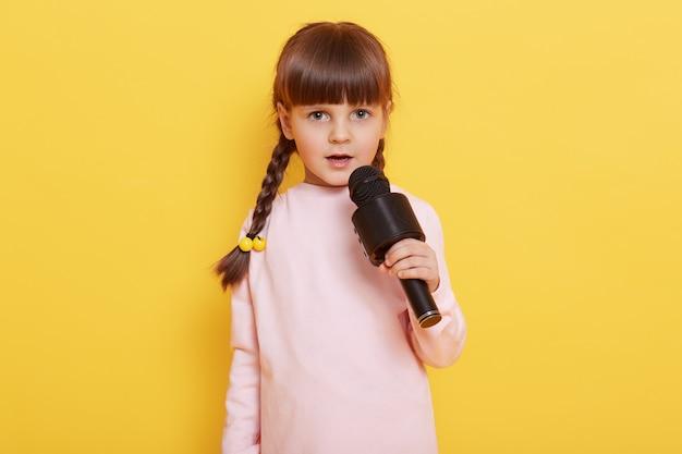 Entzückendes niedliches kind mit mikrofon in den händen, die lieder singen, schaut auf kamera, führt isoliert über gelbem hintergrund durch, kind arrangiert konzert, singt in karaoke.