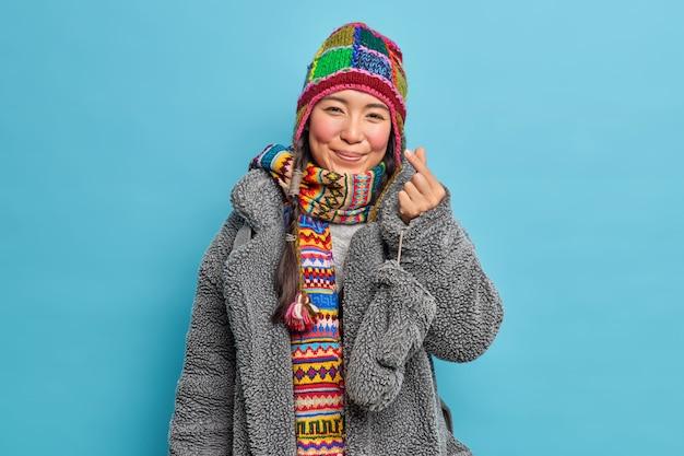 Entzückendes ostasiatisches mädchen, gekleidet in winterkleidung, macht koreanisches wie zeichen zeigt mini-herz drückt liebe aus, die gehen posen gegen blaue studiowand haben wird