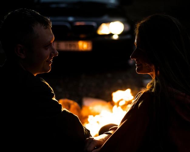 Entzückendes paar, das lagerfeuer genießt
